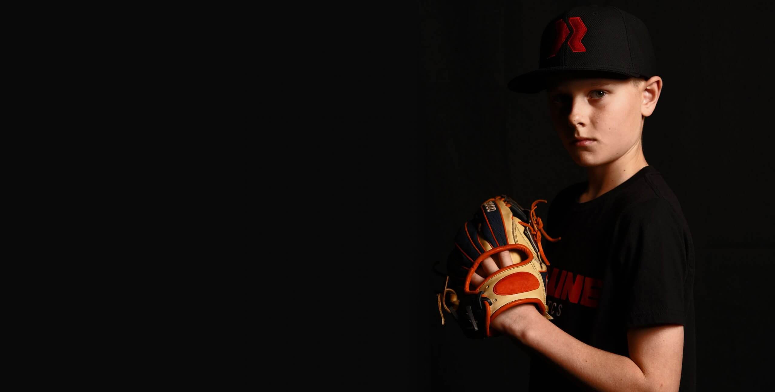 Young boy holding a baseball in a glove.
