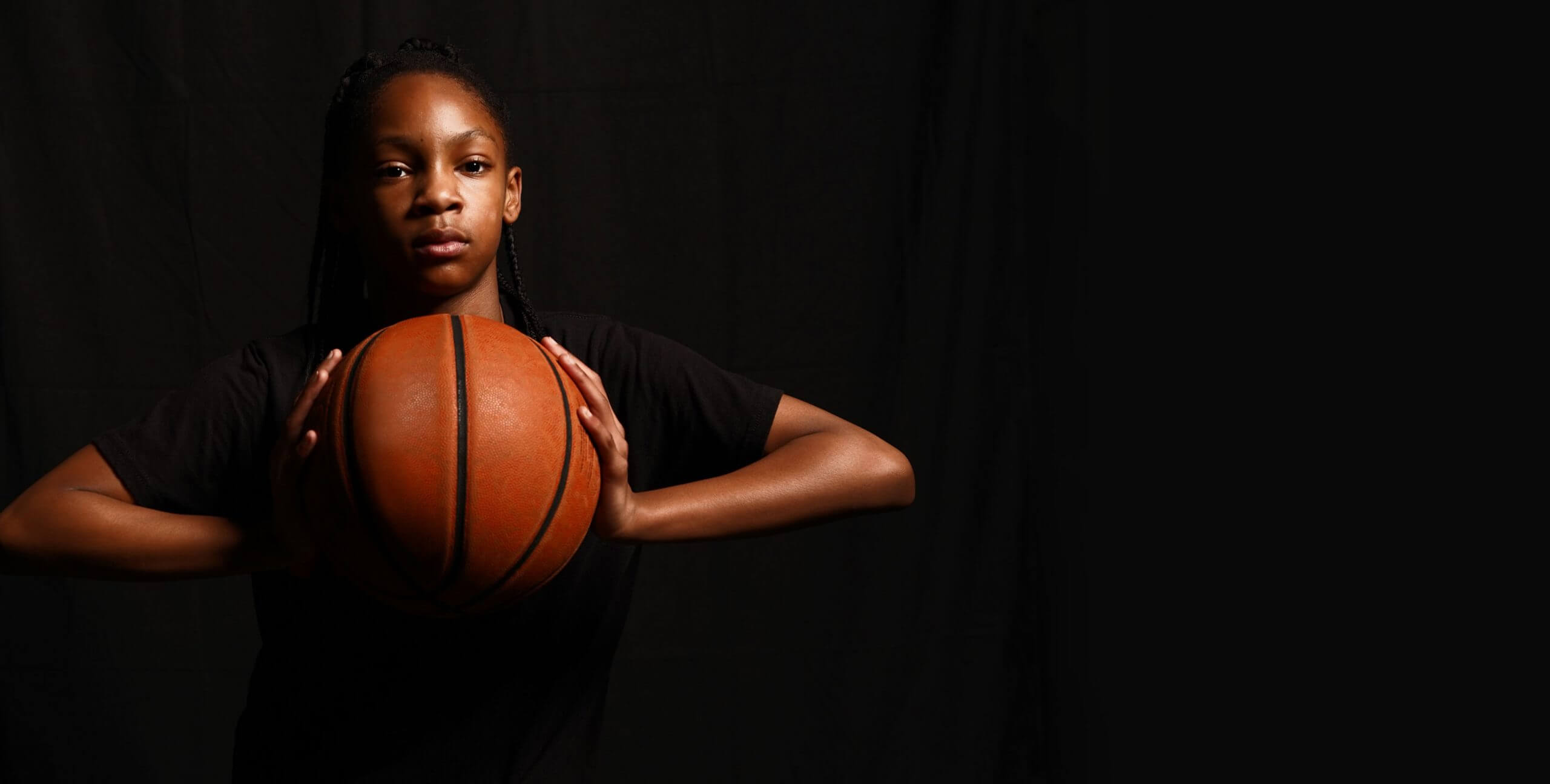 Young girl holding a basketball. Athletes perform on the field of play.