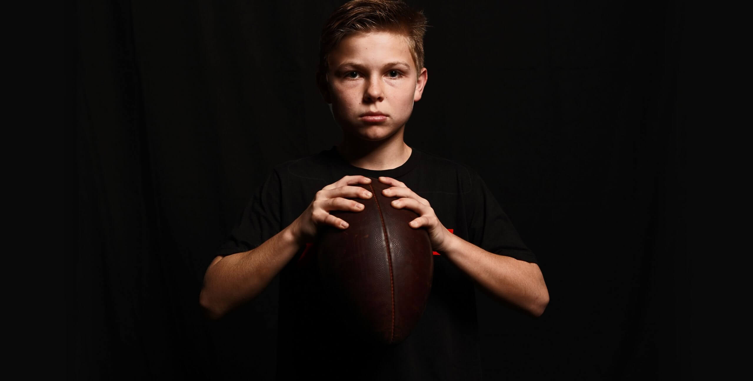 Young boy holding a football.