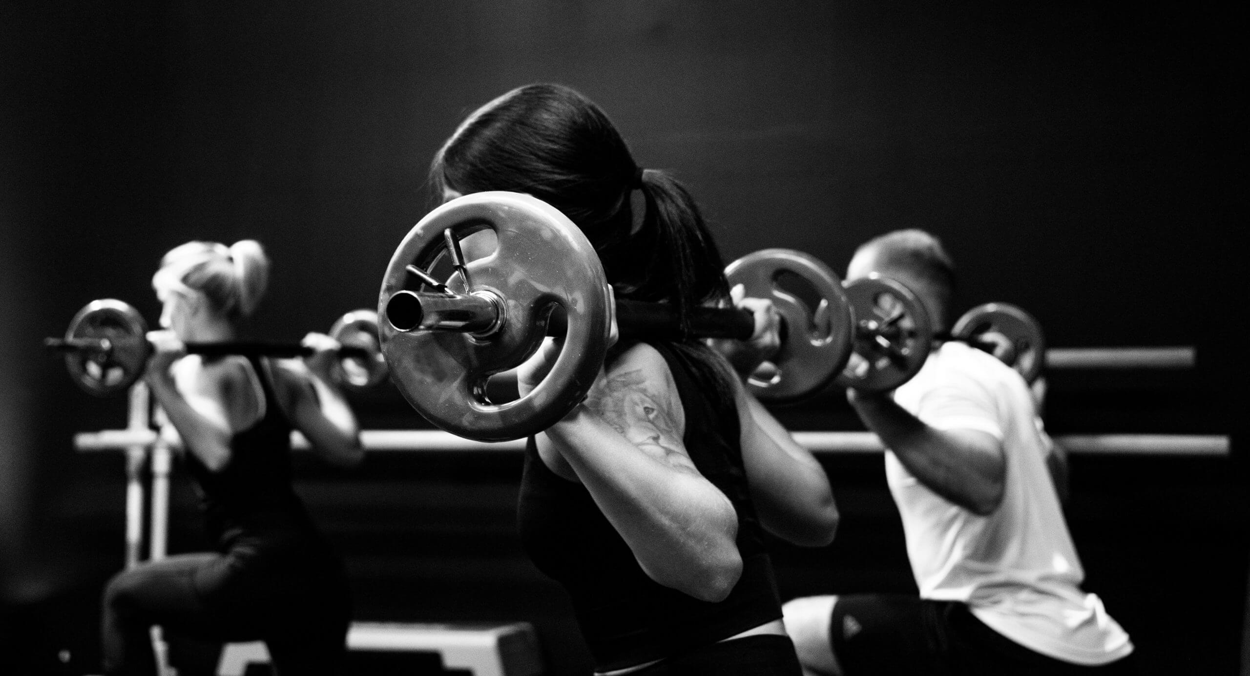 Adults doing squats. Adult fitness training.
